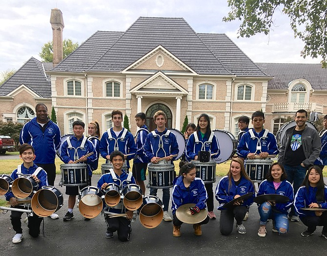 Members of the Winston Churchill High School Drumline wait for the Potomac Day parade to begin.