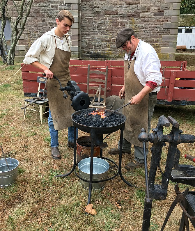 Blacksmith Eric Johnson, right, and apprentice Josiah Bloom demonstrate their craft to visitors at Great Falls Park Sunday.