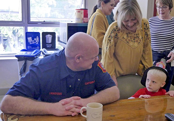 Ryan Pavelich sits at the firehouse kitchen table with Captain Lightfoot.