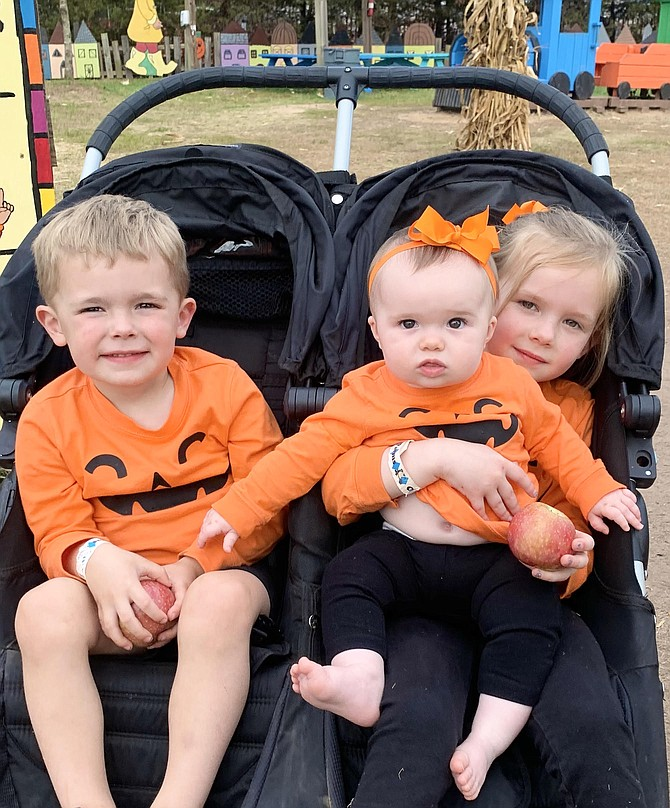 From Aldie, siblings Connor, 3, Natalie, 8 months, and Hannah, 5, play in the Kiddie Zone at Cox Farms fall festival.