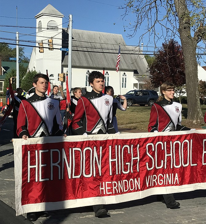 Members of the Herndon Band: The Pride of Herndon hold the parade banner announcing the 2019 Herndon Homecoming Parade.