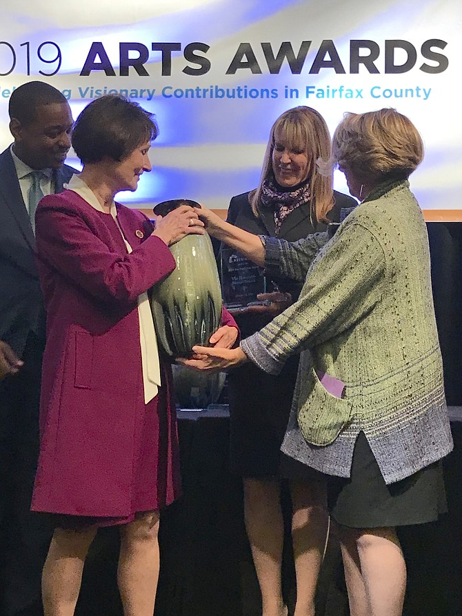 Sharon Bulova, Chairman of the Fairfax County Board of Supervisors, accepts both her crystal award and ceramic vessel created by artist Bikki Stricker of Falls Church, from Linda S. Sullivan, President and CEO ARTSFairfax, in recognition as the 2019 Honoree for the Jinx Hazel Arts Award.