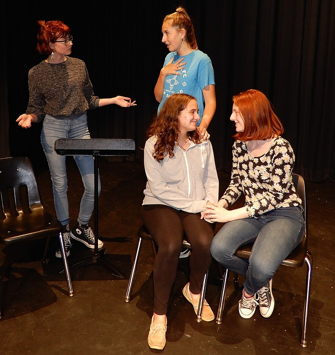 "Rehearsing a scene from Woodson High's ""Letters to Sala"" are (standing, from left) Rebecca Heimbrock (Ann) and Rachel Furr (Ann's daughter) and (sitting, from left) Rebecca Sitrin (older Sala) and Anna Riley (Ann's other daughter)."