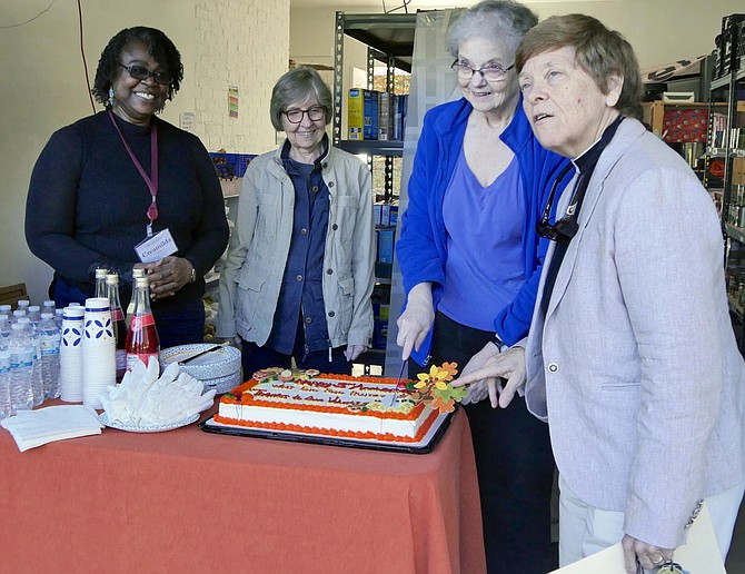 Cutting the birthday cake at West End Pantry, Monday, October 28. From left: Creamilda Yoda, parish administrator and first year seminary student, Louise Bennett, Kat Turner, Rev. Jo Belser, Church of the Resurrection.