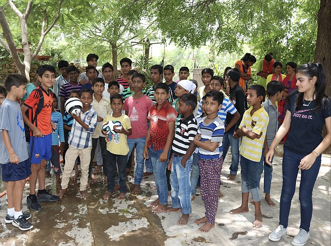 Kushaan (second from left) and Medhnaa Saran (right) visit with the children of Bal Ashram in India.