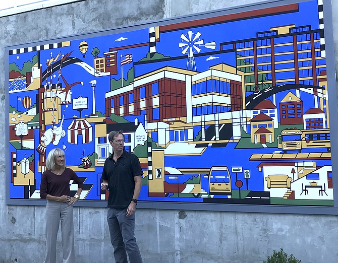 "Reston Artist Dana Scheurer, who designed ""Bailey's Crossroads Community Mural,"" for Bailey's Shelter and Supportive Housing in Falls Church, joins mural installer Brian King, owner of Artifice, Inc. in Arlington, at the mural's unveiling on Oct 24."