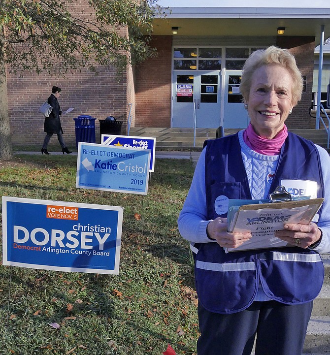 Judy Connally, former Virginia State Delegate, hands out sample Democratic ballots at Madison Community Center voting site. She says although there has been a steady stream of voters, the absentee vote was very healthy this year.