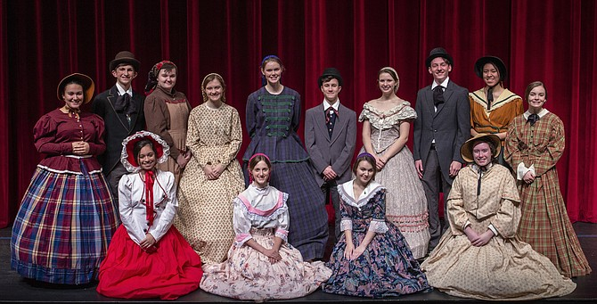 "The cast of ""Little Women"" (kneeling in front L to R): Sofia Cruz (Annie), Melanie Becker (Amy), Sophie de Waal (Meg), and Allison Dunnegan (Sallie); (standing in back L to R): Maya Andersen (Aunt March), Owen Peters (Theodore Lawrence), Caroline Coffin (Hannah), Samantha Fisher (Beth), Kathleen McNerney (Marmee), Andrew Comlish (Mr. March), Dagny Scannell (Jo), Patrick Byrns (John Brooke), Janet Le (Mrs. Gardener), and Quinn Doyle (Belle)."