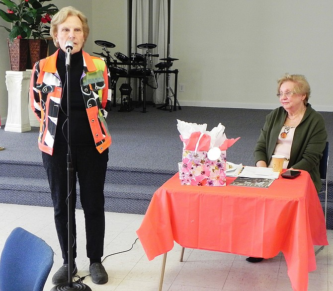 Carole L. Herrick speaks at a meeting of The Woman's Club of McLean as Club President Cecilia Glembocki looks on.