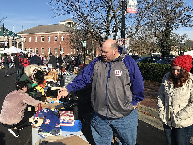 As a possible buyer looks through his items at the Herndon Downtown Community Yard Sale, seller Kirk Denino of Reston explains to Stephanie Moore-Brewer of Herndon Parks and Recreation how he decluttered.