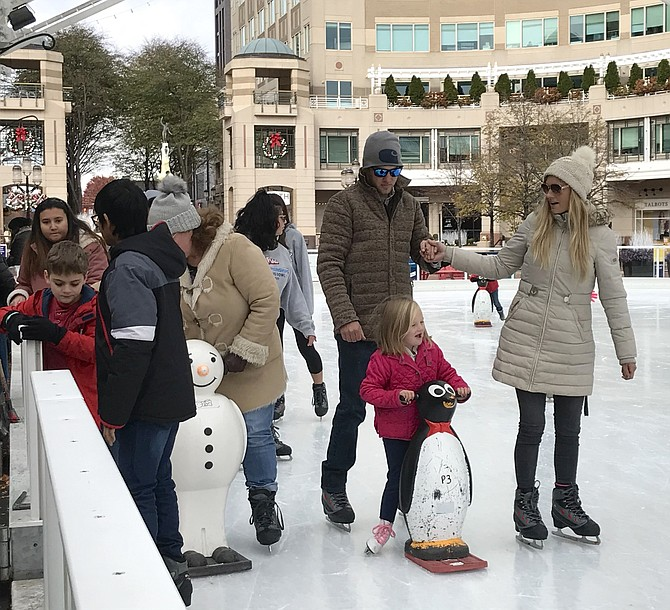 Cole Hilling, Savannah Myzk and Denver, 5, have the outdoor ice-skating requirements down pat: puffy coats, penguin skate-aid, a little hand-holding and smiles during the 2019 opening weekend for Reston Town Center public ice-skating at the Pavilion.