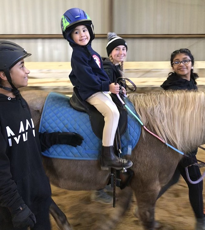 "Rider Aaron Ho, 5, of Fairfax, Naomi Jacobs, 11, of Fairfax, Elena Brunori of Vienna, and Sagarika Kagicha, 13, of Fairfax at ""Ride4SPIRIT,"" held Sat., Nov., 9, Frying Pan Farm Park Equestrian Center, Herndon."