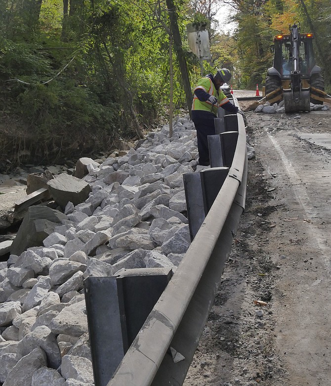 Bulldozers work to restore Chain Bridge Road, which was blown up by a burst water pipe early Friday morning. The pipe burst just under where the bulldozer is working on Saturday morning, blowing the road apart, gushing down the side of the road and taking down the railing.