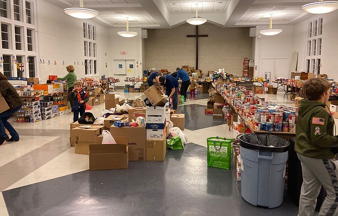 Cub Scouts and volunteers sort donated food following their participation in 'Scouting for Food in the Fight Against Hunger.'