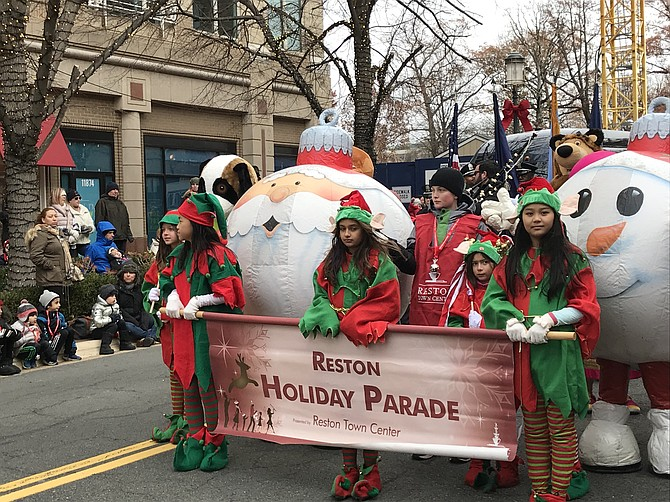 The sight and sounds of the 2018 Reston Holiday Parade kicked off with the official banner and characters.