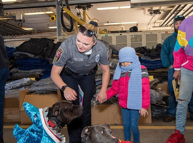 Holding the hand of a Fairfax County Police officer, a Gum Springs preschooler visits with the Caring Angels therapy dogs at the Fairfax County Firefighters coat drive distribution Oct. 28 at Fire Station 11.