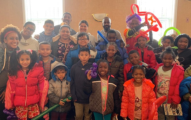 Children from the Charles Houston Recreation Center gather for a photo to show off their new coats at the Nov. 9 coat drive distribution at the Departmental Progressive Club.