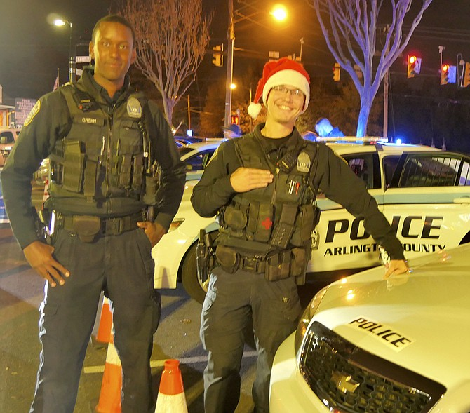 Corporal J. Green and Officer Glenn Foust join a team of seven Arlington County Police officers manning their police cruisers Thursday night at the Harris Teeter parking lot.