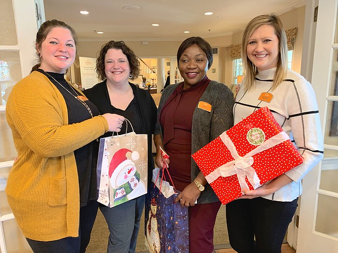 Gathering gifts for a visit from Santa's motorcade to Sunrise of Arlington are Amanda Sylvester Williams, Lisa Johns, Bora Bisimwa and Lauren Webster. The toy drive motorcade will arrive Dec. 7 between 9-10 a.m. and will benefit Easter Seals children.