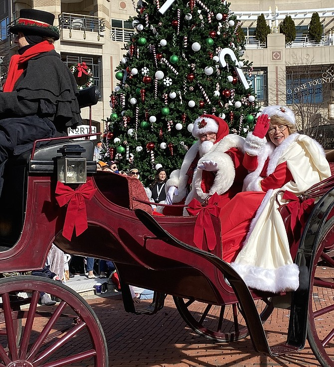 A jolly Santa Claus and Mrs. Claus arrive from the North Pole to Reston.