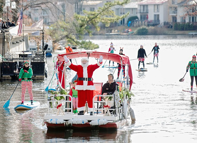 "Accompanied by elves on stand up paddle boards, Santa sets course for the Lake Anne Plaza dock, Reston to participate in ""Jingle on the Lake."""
