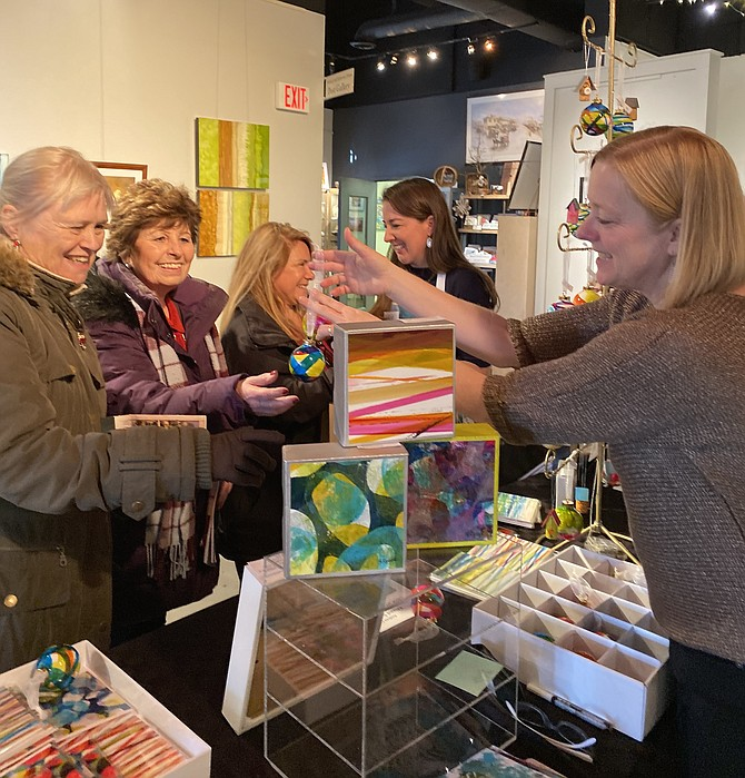 Artist Andrea Cybyk shows Marilyn Szoke, Cheyenne Cashin, Caroline Walgren and fellow artist Kat Rodgers her hand-painted ornaments at the Holiday Gallery Shop in ArtSpace Herndon during the 2019 Holiday Homes Tour of Herndon.