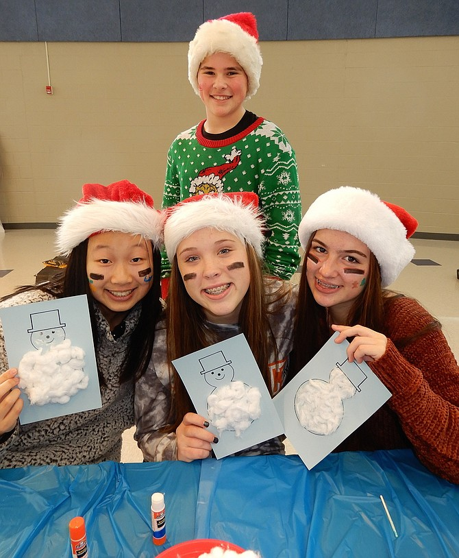 Rocky Run eighth-graders (standing) Tyler Zarybnisky and (sitting, from left) Linda Gu, Kendall Viar and Amelia Hamby helped children make holiday crafts at Raise the Ram Winterfest.