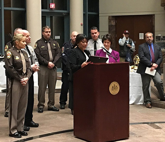 Shirley Ginwright, chairman of the Communities of Trust, presents a plaque to Sharon Bulova (in purple) while law-enforcement personnel, including Sheriff Stacey Kincaid, Police Chief Ed Roessler, MPO Wayne Twombly and Major Dean Lay, look on.