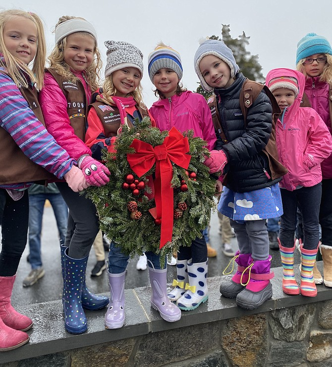 From left, Brownie Girl Scouts Troop 70091: Clare Arunski, Morgan Faust, Ellie Fair, Taylor Rommell, Abby Proudfoot, Harper Rommell, and Eleanor Beyhl hold a Remembrance wreath before the start of the Wreaths Across America 2019 ceremony at Chestnut Grove Cemetery in Herndon, Saturday, Dec. 14.