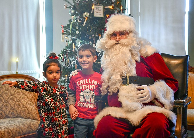 Shay, 2, and Devin Aggerwal, 4, tell Santa what they want for Christmas.