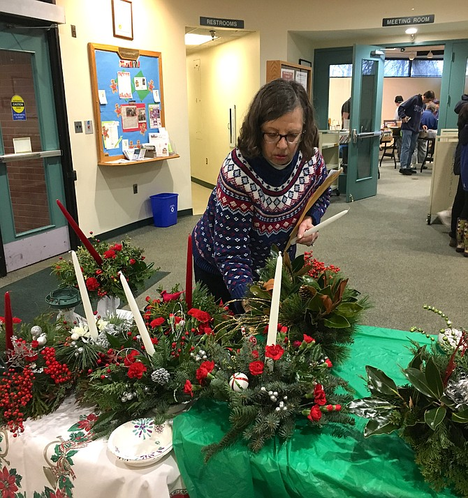 Carol Dietzel adds candles to arrangements at the annual Potomac Village Garden Club Holiday Greens Arrangements sale Saturday.
