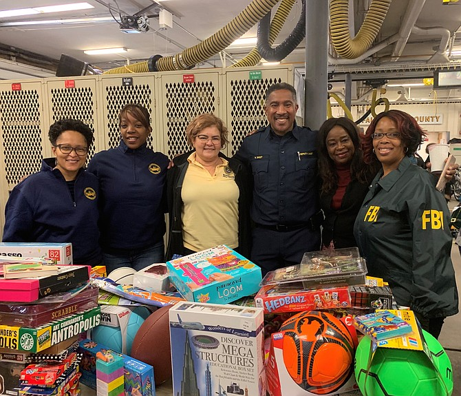 Fairfax County Fire and Rescue Deputy Chief Willie Bailey, third from right, and founder of the annual toy drive, poses with volunteers from the D.C. Field office of the FBI.