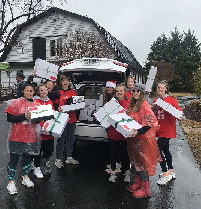 Local teens unload  more than 1,000 gifts from Wish List Angels at the Dec. 15 drive-through drop-off.