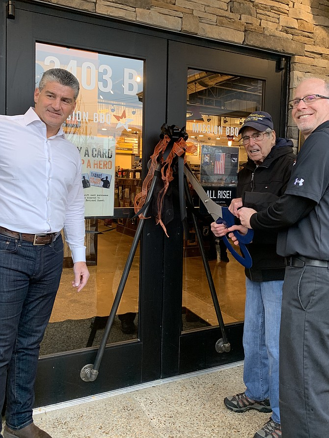 Retired Air Force Colonel Robert A. Shawn takes part in the ribbon-cutting ceremony, celebrating the opening of MISSION BBQ located at 2403B Centreville Road, Herndon, on Dec. 16. Host and co-founder of MISSION BBQ, Bill Kraus, lends support, as does General Manager, Adam Faggio.
