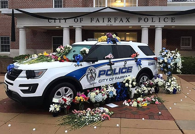 Black bunting is draped across the police station, while a floral memorial adorns this police car in Sgt. Moskowitz's honor.