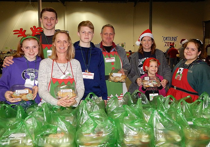 Each gift recipient received a box of handmade cookies. Manning the cookie station on delivery day are (from left) the Gunn family: Catie, Charlie, Carole, Sean and Charlie Sr.; plus Megan Girardin and daughter Julia, 7, and Mary Allison.