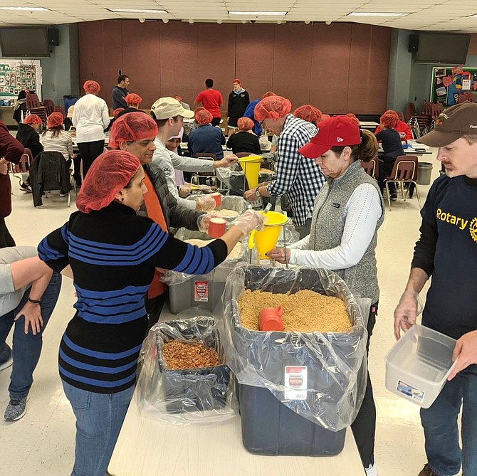 Many hands make quick work of filling, weighing, sealing and packing 10,152 counted meal bags during the Rotary Club of Reston's service project partnering with Rise Against Hunger.