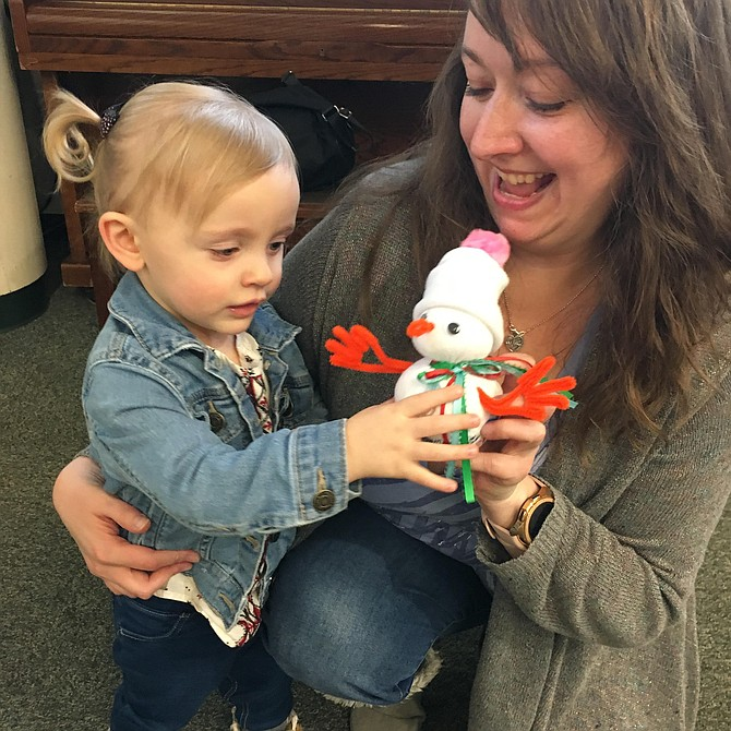 Angels Macri and her 22-month-old daughter Dorothy Ellen play with the snowman they created during the Potomac Library Build a Snowman project.