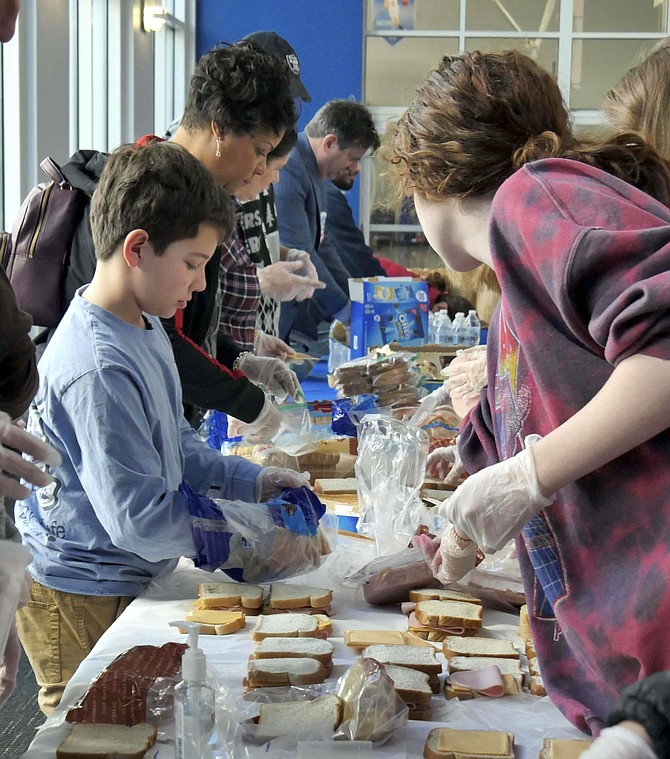 Volunteers of all ages make bologna and cheese sandwiches to fill 200 brown paper bags for delivery to Arlington homeless.