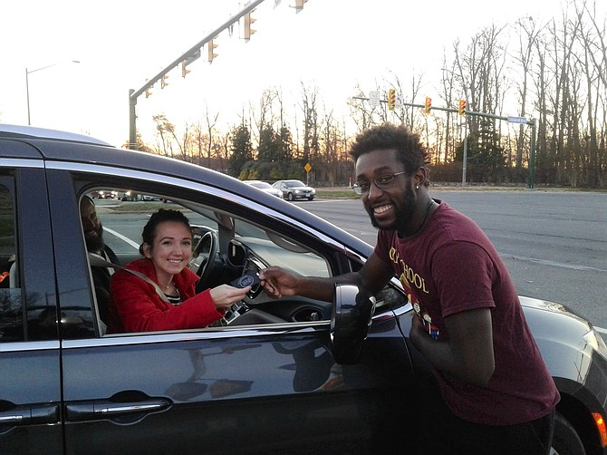 """Stephanie Brewer, left, invites street performer Chris Conway to attend holiday services of the New Life Christian Church at 14550 Lee Road in Chantilly.  Brewer and her family have seen Conway dance at traffic intersections in Centreville and Chantilly.  """"We see him all the time and the kids love it,"""" Brewer says Dec. 15."""