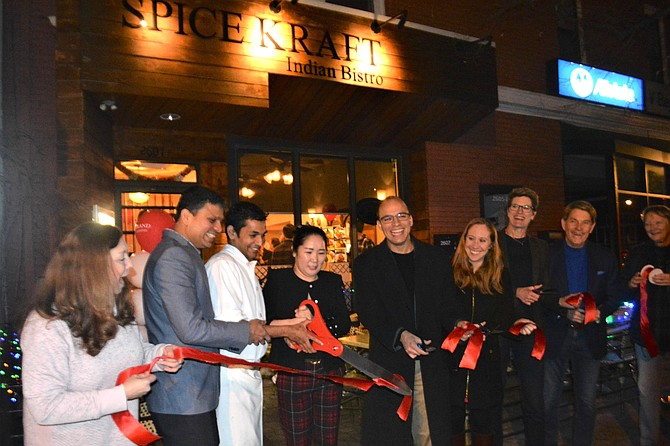 Mayor Justin Wilson, center, is joined by city officials and members of the Del Ray Business Association Jan. 20 as he cuts the ribbon to formally open Spice Kraft restaurant on Mount Vernon Avenue.