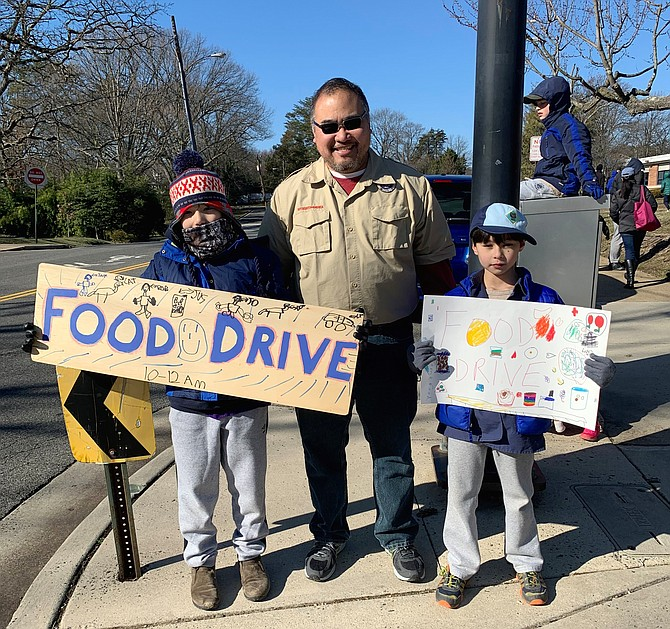 Cub Scout Pack 801 leader Stephen Ng, center, with pack members Edward Ng and Alex Morris at the Jan. 20 food drive for ALIVE! at Douglas MacArthur Elementary School.