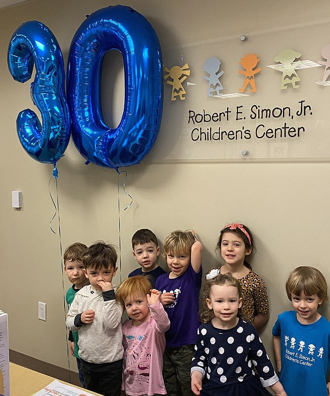 Children at the Robert E. Simon, Jr. Children's Center (from left): Nathan Weber, 2, of Vienna, Will Riordan, 4, of Reston, Campbell Catlett-Miller, 2, of Reston, Isaac Younger, 4, of Fairfax, Russell Wigen, 4, of Sterling, Beatrix Schimpf, 3, of Reston, Ava Leshock, 5, of Great Falls and Rainier Gramsky, 3, of Great Falls mark the milestone 30th anniversary of the center with big Mylar balloons soaring over their heads.