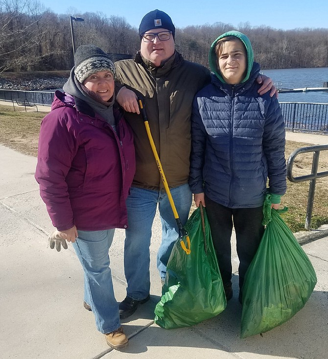 From left:  Brian, Tatiana and Thomas Lisle of Springfield participate in the Friends of Lake Accotink Park volunteer clean-up event on Monday, Jan. 20, 2020.