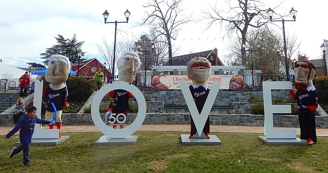 The Washington Nationals' racing presidents posing for photos by the LOVE letters in Old Town Square.