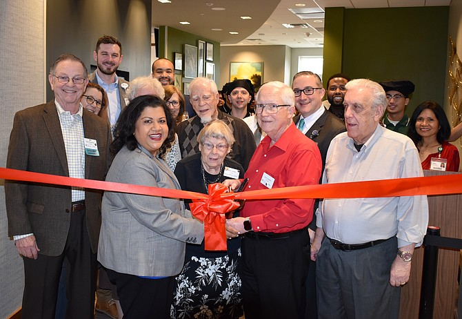 From left: Roy O'Connor, Greenspring Resident; Chandra Kumar, Executive Director; Betty Griffin, Resident; and Clint Lambert, Resident, do the honors in front of a crowd of residents and staff who gathered for a ribbon-cutting ceremony at the grand re-opening of the senior living community's Potomac Café.