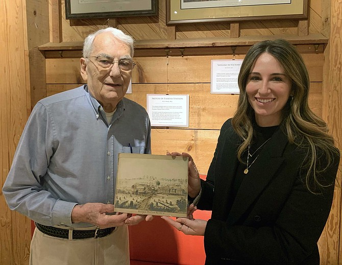 Station President, Jack Migliaccio, accepting the rare Civil War sketch of the historical Fairfax Station area from Kayla Gray Smith.