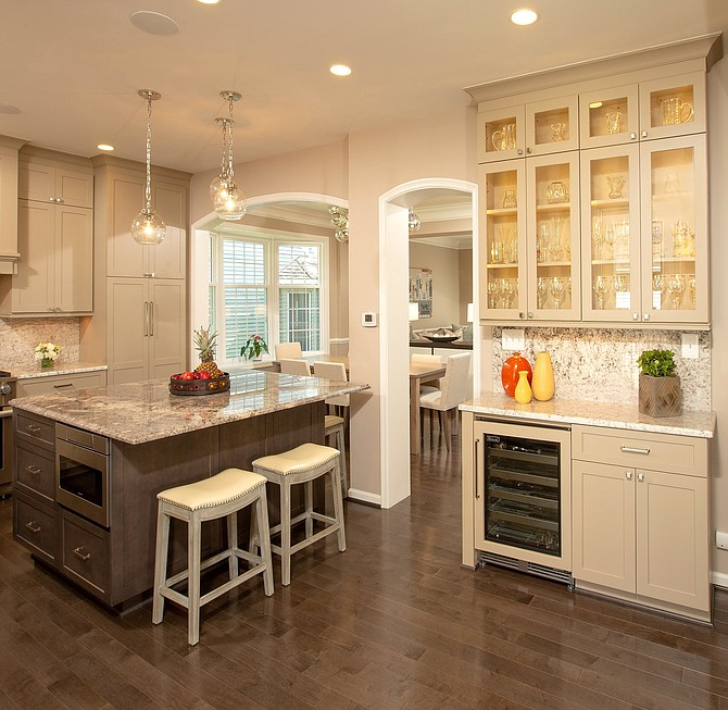 To generate more light and living space in a circa 1990s house, Sun Design Remodeling removed a wall between the kitchen and great room. A granite food prep and dining counter replaces a stand-alone breakfast table. The wine refrigerator is convenient to the re-designed family room.
