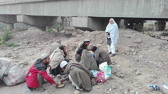 Maryam Bibi serves a morning meal to drug addicts this year in Pakistan.