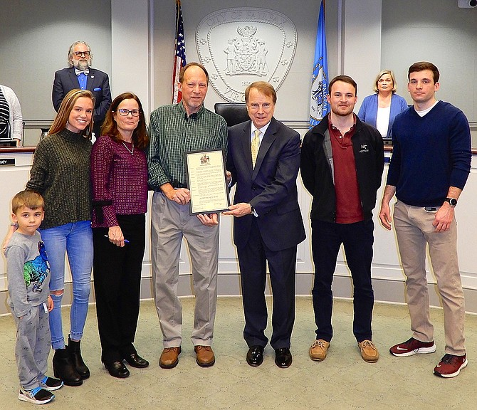 Honoree Scott Peirce (green shirt) with (from left) nephew CJ Ray, daughter Rachel Peirce, wife Mary McCullough, Mayor David Meyer, and sons David and Brian Peirce. (In back are Council members Michael DeMarco and Janice Miller).